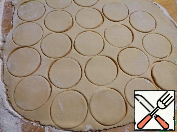 Roll out the dough into a thin layer, 0.5 cm thick. Cut out the circles.