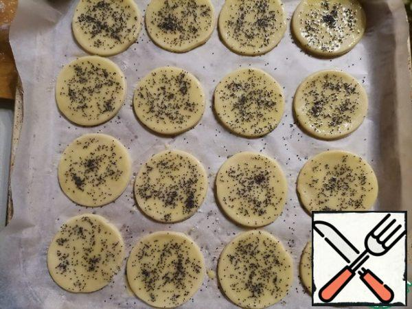 Cover the baking sheet with parchment and lay out the circles. Brush them with egg yolk and sprinkle with poppy seeds.