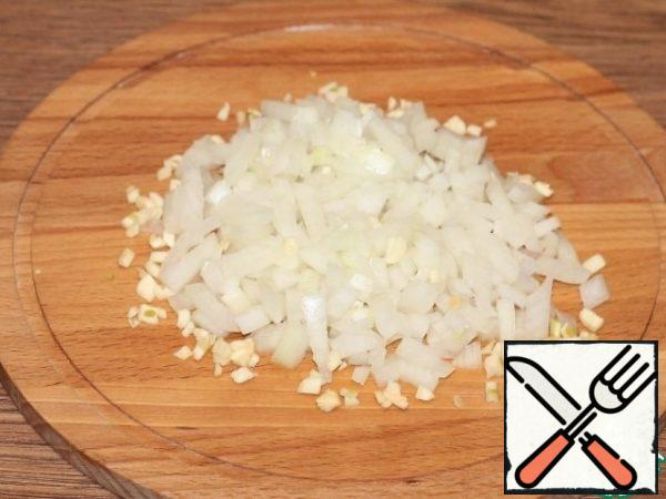 """Let's prepare the vegetables. Finely chop the peeled onion and garlic and fry in hot oil until """"transparent""""."""