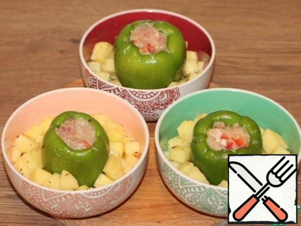 Lay out the potatoes in tins. Put the peppers in the middle.