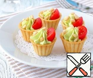 Add cooked avocado sauce to the tartlets, add cherry tomatoes, sprinkle the structure with pine nuts on top.