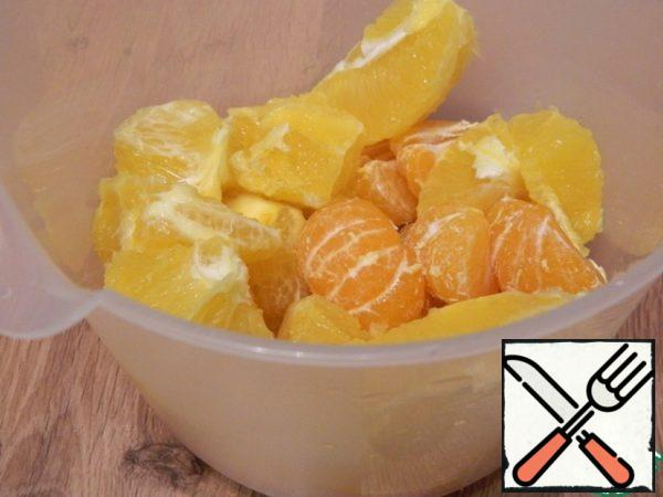 Let's peel the orange and tangerines. Place in a tall bowl. Grind with a blender.