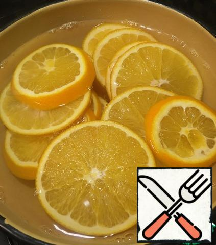 Oranges cut into circles of 5 mm, pour boiling water for 5 minutes, this will remove the bitterness from the peel. Then cook the sugar syrup. Put the oranges in it, cook on low heat under the lid for 1 hour.