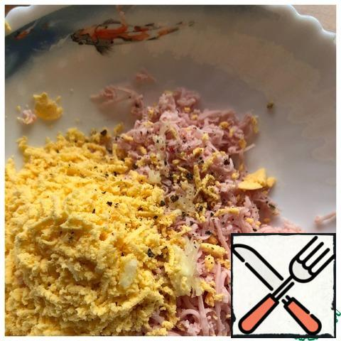 Grate the sausage and egg yolks on a fine grater. Add the garlic passed through the press and ground pepper.