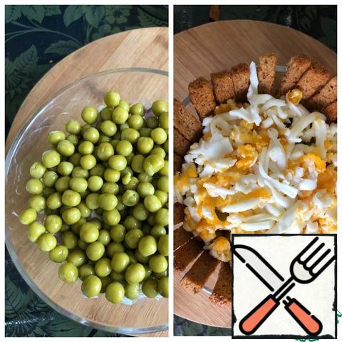 Next layer: peas and top with grated eggs on a coarse grater. Place the crackers around the circumference of the salad bowl.