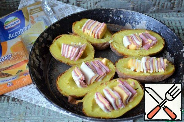 Remove part of the pulp from the potatoes, press down, making blanks, add salt. Spread the cheese and ham in the potatoes, sprinkle with paprika.