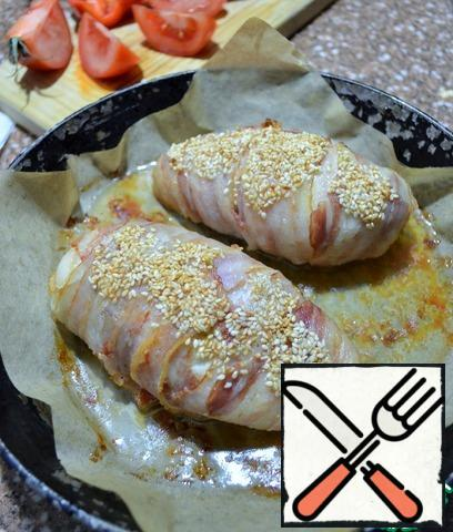 Carefully wrap the bacon, sprinkle with sesame seeds.