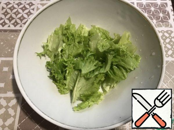 Lettuce leaves are randomly torn by hand and placed on the bottom of the salad bowl .
