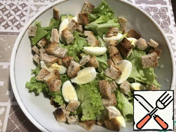 Again, we tear the salad and put it in a salad bowl. Top with crackers and quarters of quail eggs.