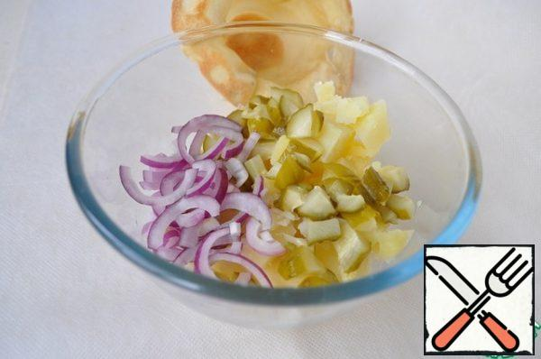 Cut the potatoes, cucumber and onion for the salad.