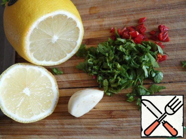 Finely chop the chili pepper, squeeze the garlic through the press, add the chopped parsley and lemon juice with olive oil.