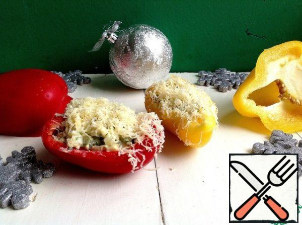 Grate the cheese on a fine grater. Put the salad in the pepper slices, garnish with grated cheese on top.