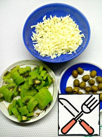 Peel the kiwi, cut into random pieces, and grate the cheese. Cheese can be taken to your liking. Olives can be taken black, if you do not like green.