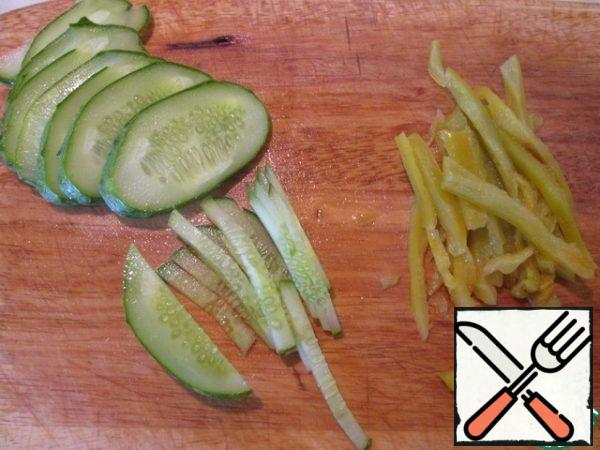 Remove the skin from a well-sweated pepper, remove the seeds and cut into 0.5 cm strips. Leave the remaining juice for refueling. Cut the cucumber diagonally into thin slices, then into 0.5 cm strips.