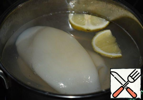 Boil the squid (defrost beforehand and peel) in boiling well-salted water with a slice of lemon for a couple of minutes. Cool down.