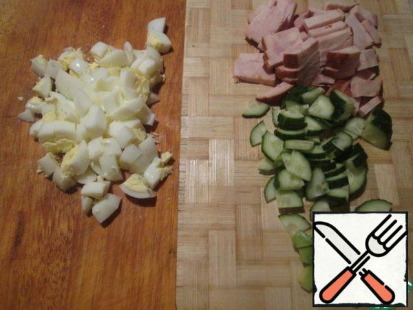 Boil the eggs, peel and cut them. Cut the cucumber and avocado into cubes, and the ham into strips.