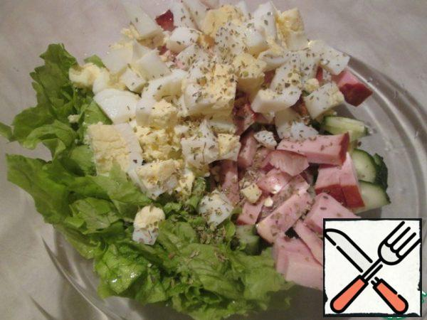 Wash the lettuce leaves, dry them, cut them coarsely or tear them with your hands. Put all the ingredients in a salad bowl, add salt, and sprinkle with oregano. For the dressing, mix the olive oil, balsamic vinegar and garlic. Pour the dressing over the salad.