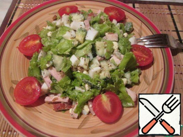 Now we spread the salad on a serving dish, sprinkle with chopped walnuts and decorate with cherry halves.
