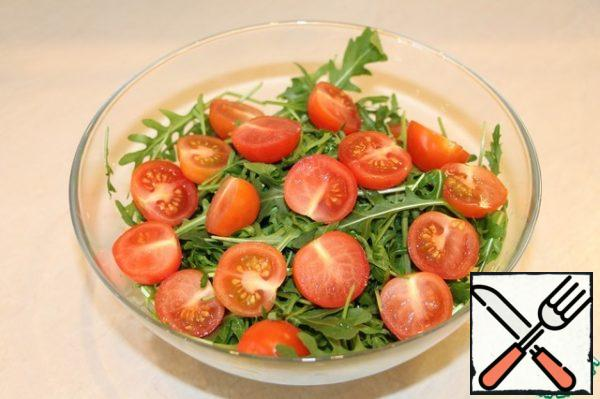Put the arugula in a large salad bowl, cut the cherry in half and add to the arugula.