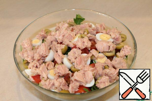 Then the olives... Mash the tuna a little with a fork in a jar and add to the salad bowl.