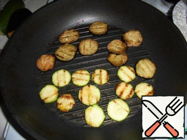 Fry the sliced zucchini and eggplant slices until golden brown in a grill pan on both sides in olive oil, season with salt and pepper to taste. Remove the vegetables from the heat. In the same pan, fry the chopped cherry halves.