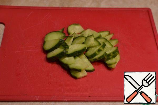 Pickled and fresh cucumbers are cut lengthwise into 4 parts and then into pieces.