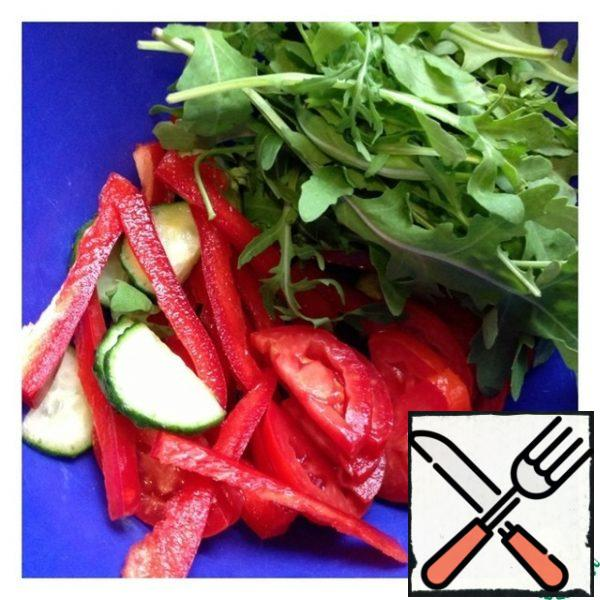 Put the arugula in a salad bowl. Cut cucumber and tomato into slices, pepper into thin strips.