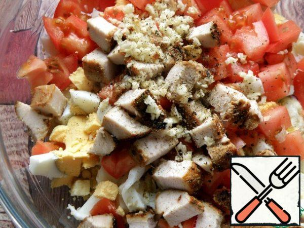 Chicken fillet and tomatoes are also cut into cubes. Finely chop the garlic and add it to the salad along with the black pepper.