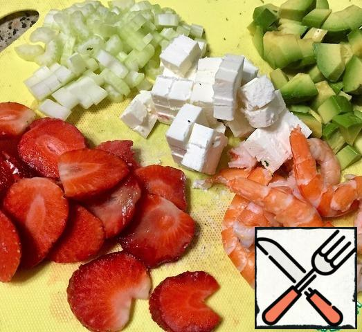 Boil the rice until tender. Boil the shrimps and peel them. Cut the strawberries into slices. Peel the celery stalk and chop the pulp. Cut the cheese into cubes. Peel the avocado and cut it into cubes.