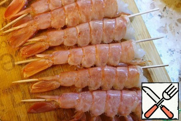 Remove the heads of the shrimps. Pass the skewer through the shrimp in the area of the esophagus. This is necessary so that the shrimp remains straight during cooking.