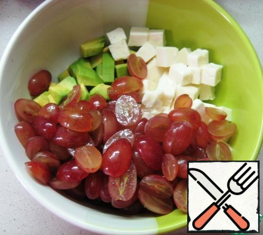 Wash the grapes, dry them, and cut them in half.