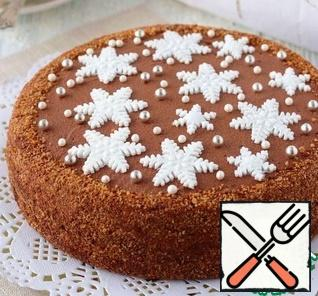 On a layer of biscuit, coffee-impregnated crust, add cream with prunes. Smear the side surface, top of the cake with cream without prunes. Decorate the cake to your liking. To decorate the cake in the recipe, confectionery sprinkles were used, snowflakes were made from sugar mastic.