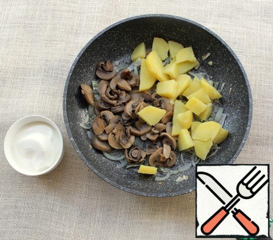 Add the mushrooms and potatoes to the onion and fry them all together for 3-5 minutes. Then add the sour cream, mix, cover the pan with a lid and then cook over low heat.