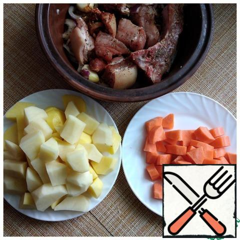Potatoes and carrots are cut into large cubes-arbitrarily.