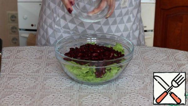 Red canned beans are drained from the jar and washed under running water. Let the water drain and pour it into a salad bowl.