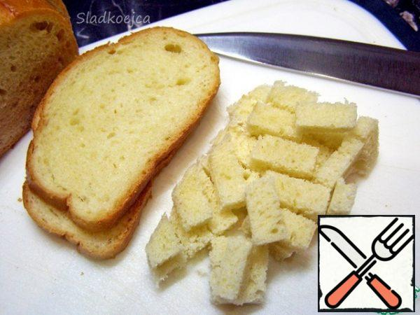For the salad, you need crackers: you can take ready-made store-bought ones, but I prefer to make them myself. It's not difficult. Cut 5-6 slices from the loaf, cut off the crust and cut into small cubes. Put the bread cubes in a deep container or plastic bag, lightly sprinkle with vegetable oil and mix. Add salt, if desired, sprinkle with garlic powder (or other spices to your taste) and mix again.