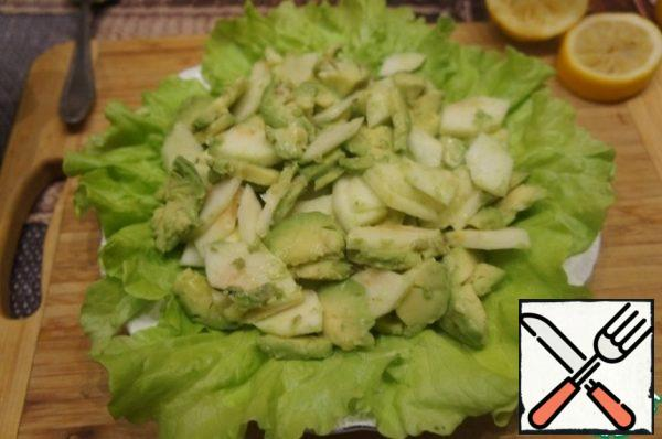 Cut the avocado in half, remove the bone, then carefully remove the pulp with a tablespoon, cut it into slices across the pieces. Sprinkle with a second spoonful of lemon juice. Mix very gently. Spread the avocado slices on the lettuce leaves.