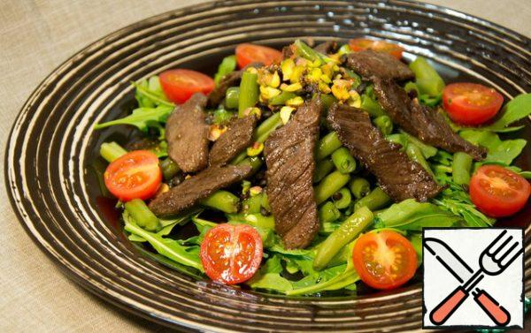 Assemble the salad: lay out a pillow of arugula, put a mixture of beans and lentils on it, and garnish with pieces of beef, pistachios and cherry tomatoes on top.