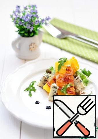 Put on a dish the seasoned mixed salad, fried mango in bacon, put the chopped blue cheese, sprinkle with parmesan, capers, ground black pepper, pour the remaining dressing, decorate with cream-balsamic.