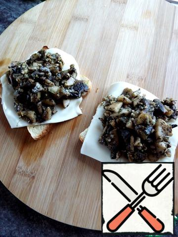 On the hot bread, put the cheese and a pile of fried mushrooms.