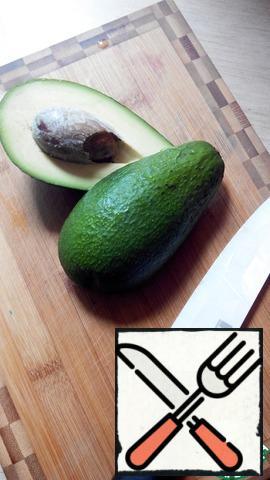 Cut the avocado in half, remove the bone.