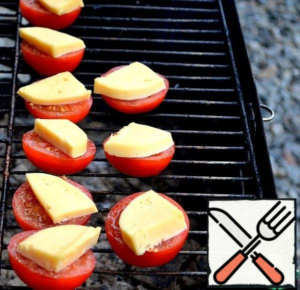 Bake tomatoes. We wait for the moment of softening of the cheese, it should not flow.