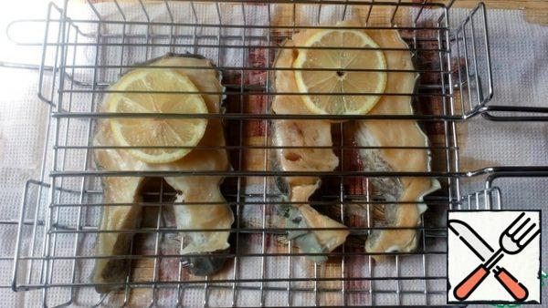 Cut the lemons into thin slices and place them on a wire rack. Put the fish on top and the lemons again. Cook the fish on both sides for about 10 minutes. The fish under the lemons will turn out juicy, with a slight sourness, but not fried. If this option does not suit you, cook without lemons.