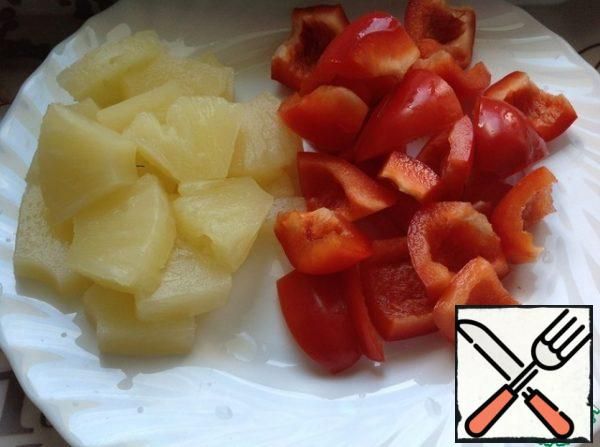 Cut the pineapple into large slices. Peel the peppers and cut them into slices.