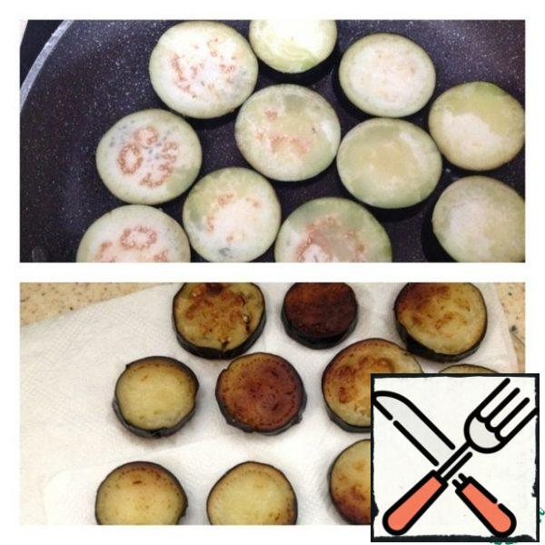 Cut the eggplant into slices and fry on both sides until cooked in vegetable oil. Put the finished eggplants on paper towels, so that there is no excess oil. By the way, eggplants do not need to be pre-soaked in salt water.