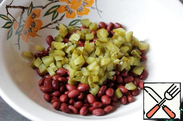 Add the pickled cucumbers to the beans, cut into small cubes (they should be the size of chopped nuts).