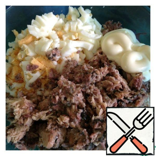 Cut the egg into cubes, add mayonnaise. With canned fish ( I have mackerel), drain the excess liquid, mash the fish with a fork.