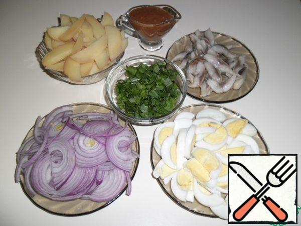 Peel the cooled potatoes and eggs and cut them into slices, half-ring the onion, and coarsely chop the arugula. Cut the herring fillet into strips.