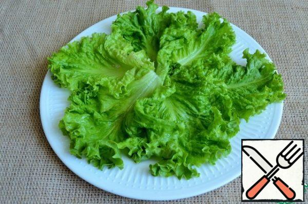 Wash the salad leaves, dry them and put them on a serving dish.