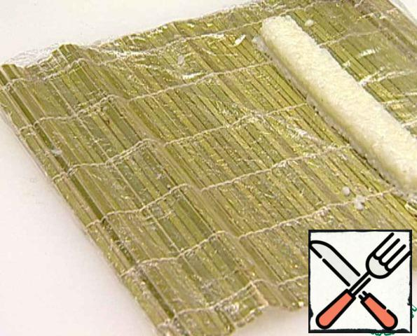 Pre-boiled rice roll up with a bamboo mat, put on a plate.